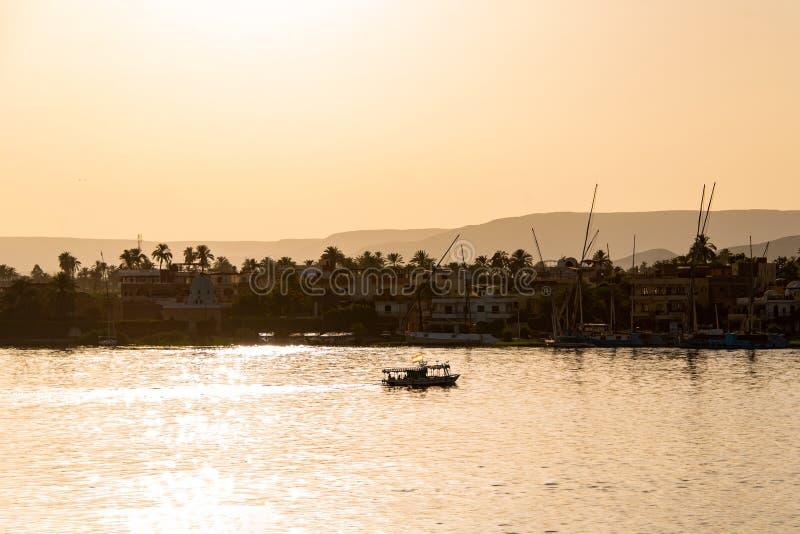 尼罗河的看法有风船的在金黄五颜六色的日落在卢克索,埃及 库存照片