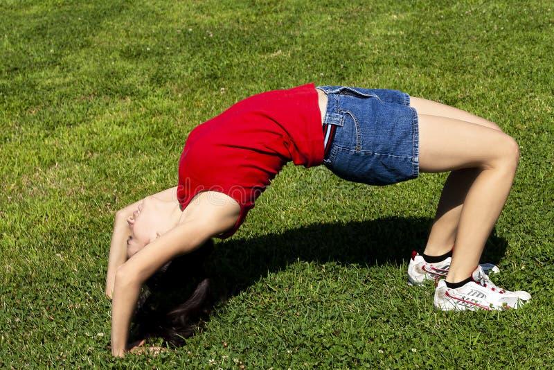尽全力在绿草的年轻西班牙妇女 库存图片