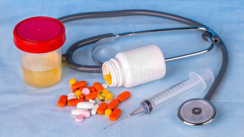 尿容器、注射器、phonedoscope和色的药片在蓝色 免版税库存照片