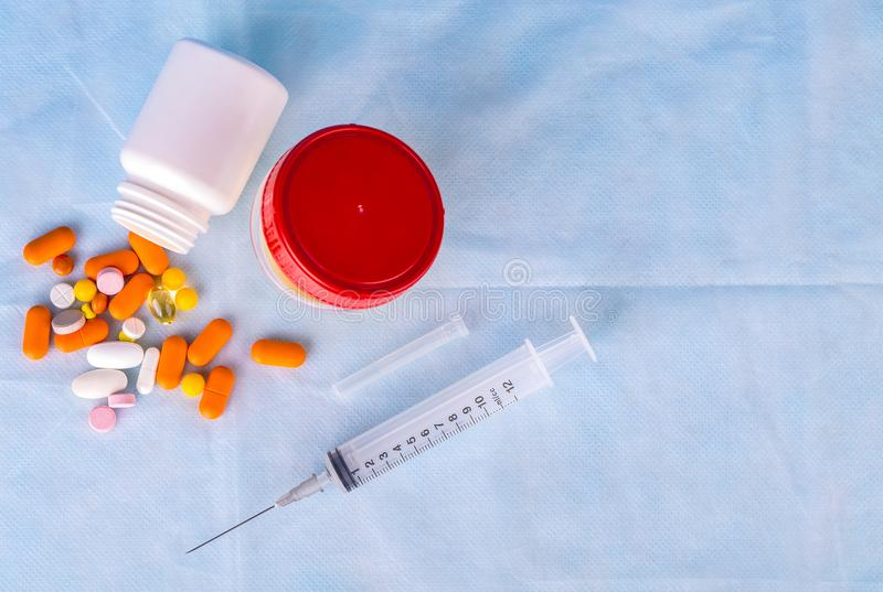 尿容器、注射器和色的药片在蓝色背景 免版税库存图片