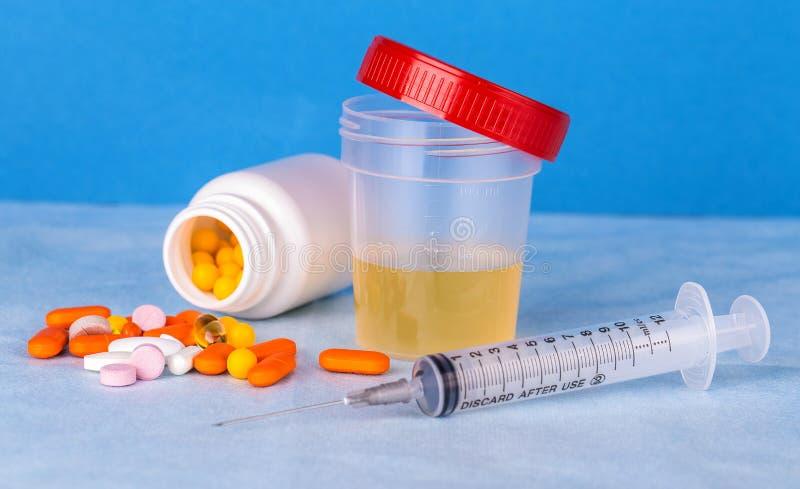 尿容器、注射器和色的药片 免版税图库摄影