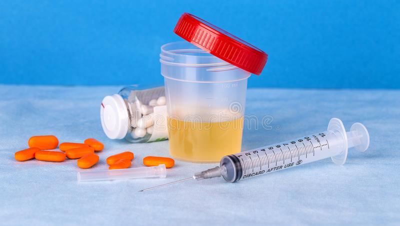 尿容器、注射器和色的药片 免版税库存图片