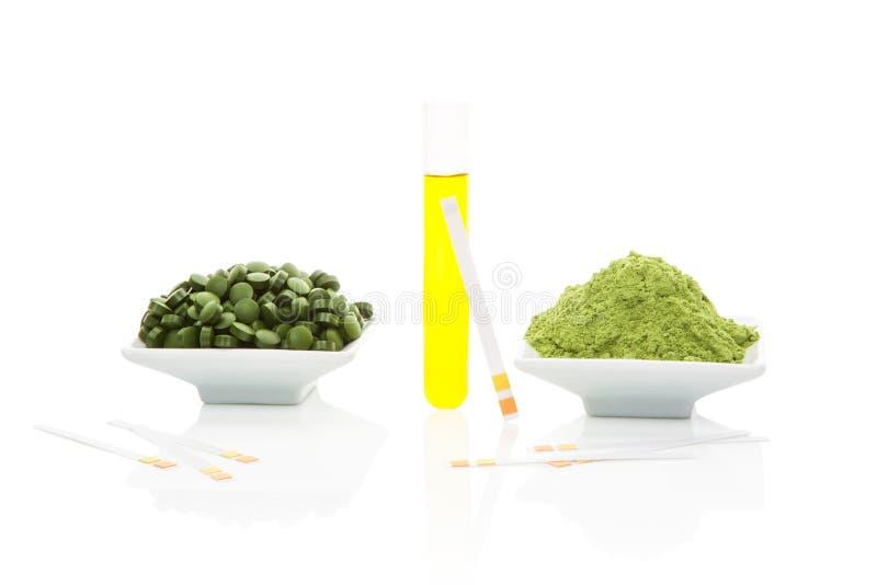 尿样、酸碱度试验片和绿色药片。 免版税库存图片