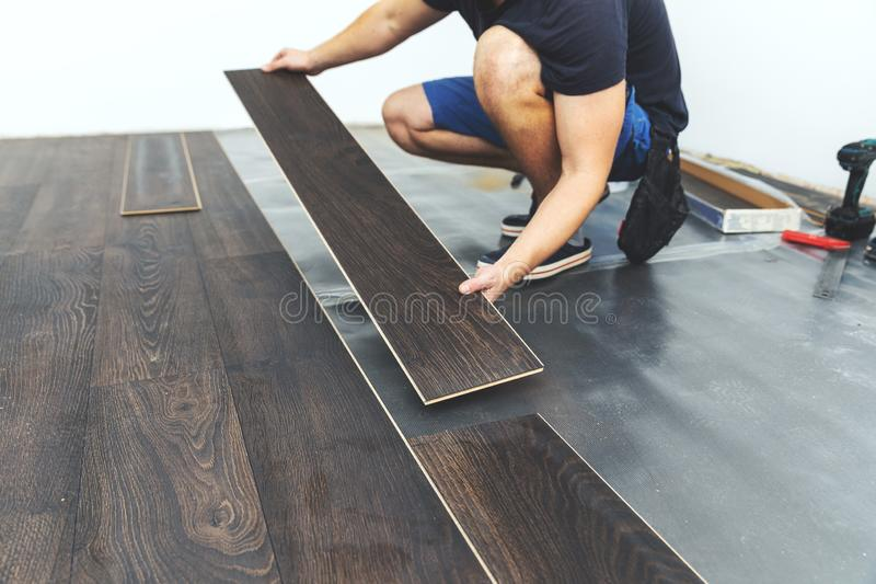 层压制品的地板-安装新的地板的工作者 免版税库存图片