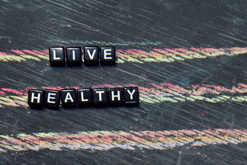 居住健康在木块 发怒被处理的图象有黑板背景 库存照片