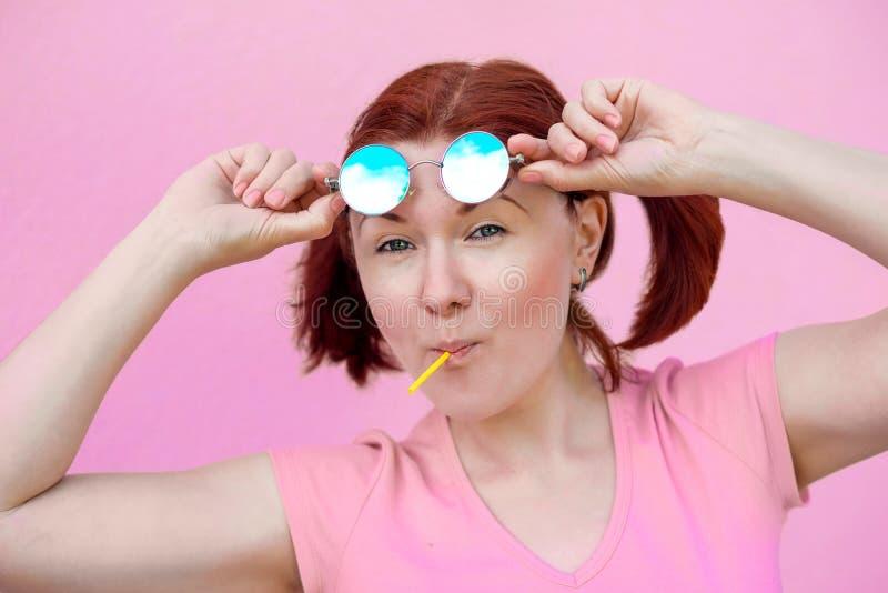 居住在生活的光明面:美女画象桃红色衬衣的有猪尾发型、蓝色太阳镜和棒棒糖的 免版税库存图片