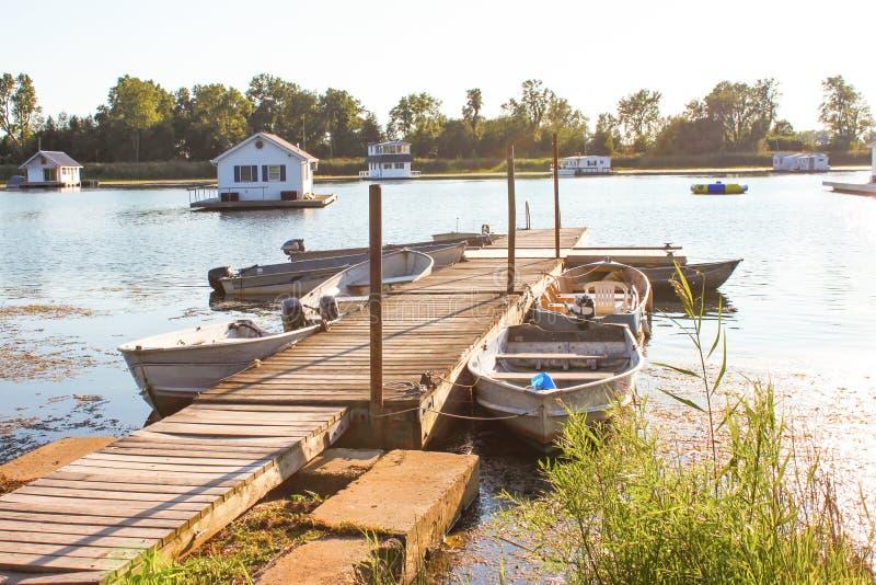 居住船在伊利湖的池塘从有划艇的船坞栓了由通入决定他们在金黄小时在一个夏日 免版税库存照片