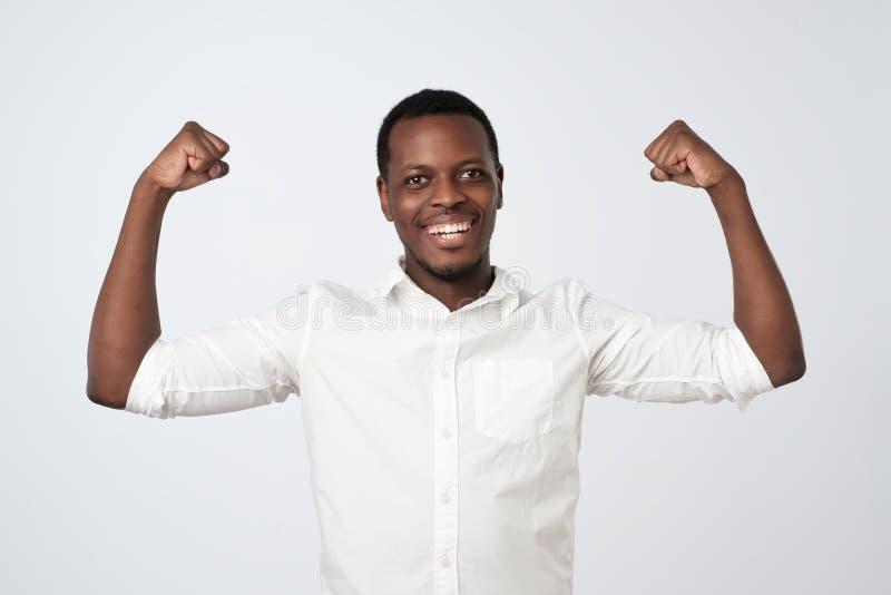 屈曲二头肌的白色衬衫的坚强的年轻非洲人 看多么强和健康我是 库存图片