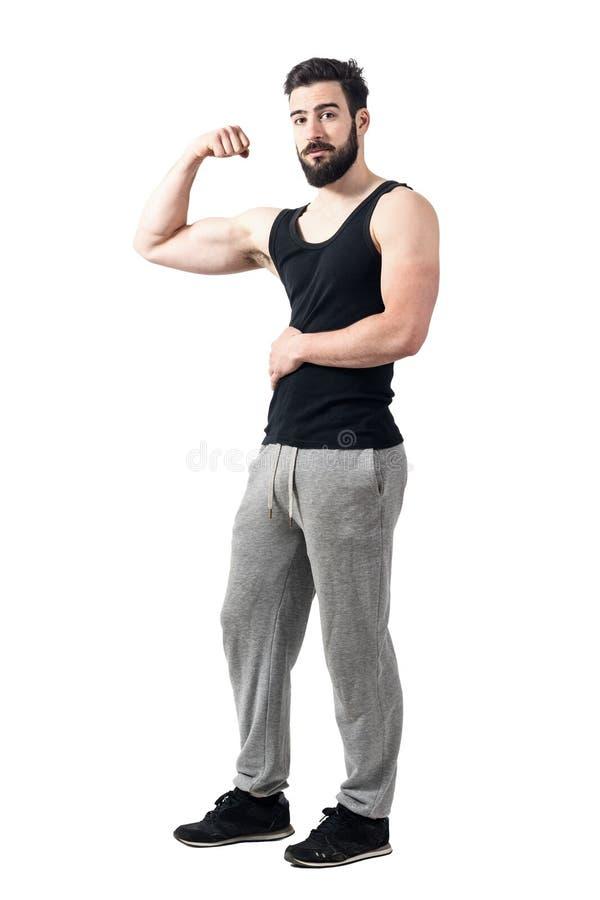 屈曲二头肌肌肉的无袖衫的运动员看照相机 库存图片