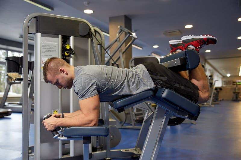 屈曲在健身房机器的人腿肌肉 库存照片