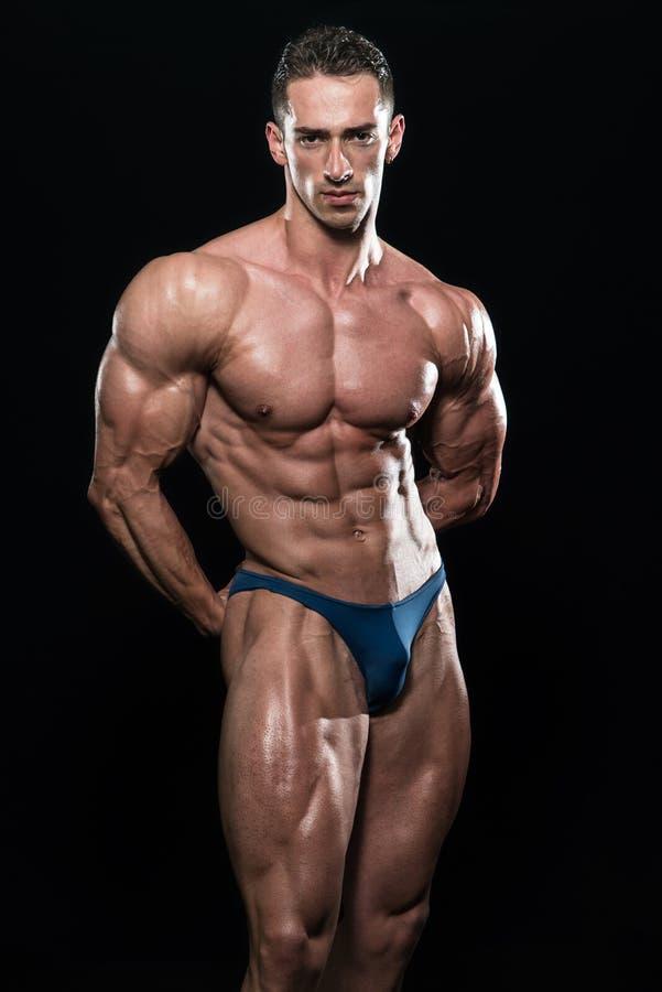 屈曲在黑Blackground的年轻爱好健美者肌肉孤立 库存照片