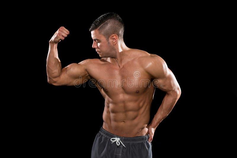 屈曲在黑Blackground的年轻爱好健美者肌肉孤立 免版税库存照片