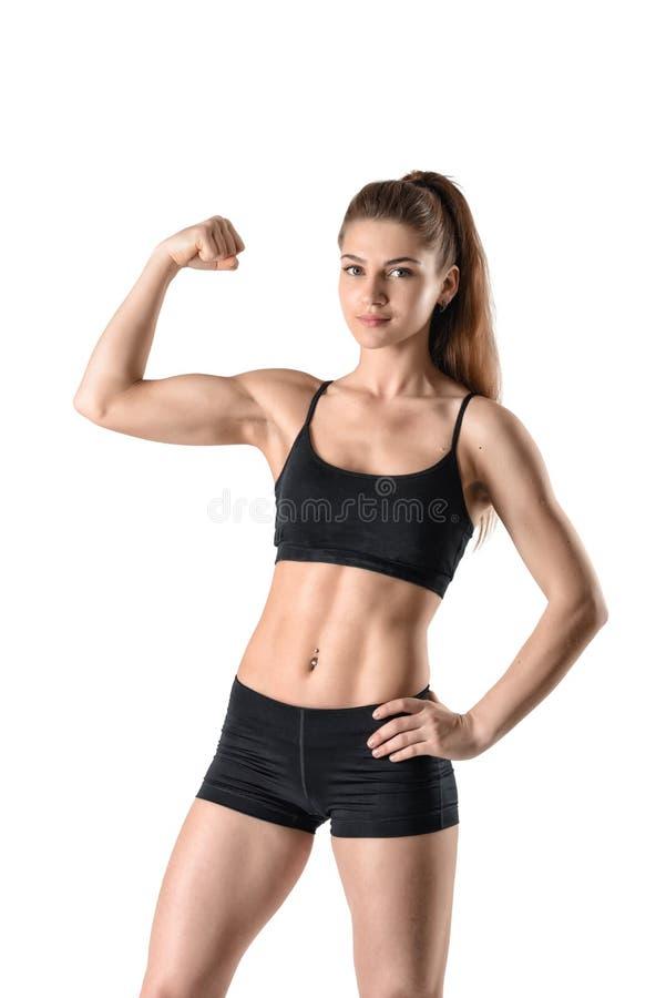 屈曲她的二头肌的年轻坚强的肌肉妇女保险开关画象  免版税图库摄影