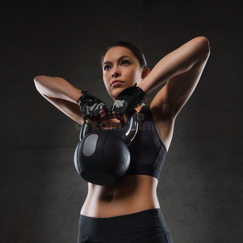 屈曲有kettlebell的少妇肌肉在健身房 免版税库存图片