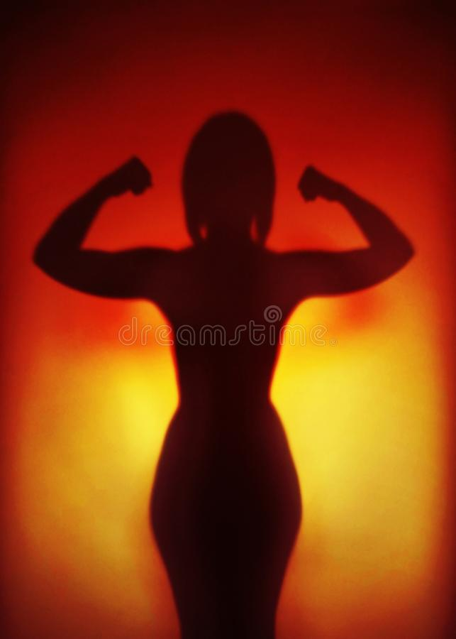 屈曲肌肉的一名坚强的妇女的女性援权概念剪影 免版税图库摄影