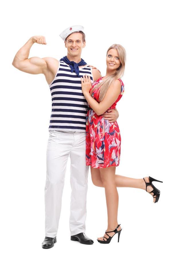屈曲他的二头肌和摆在与女朋友的水手 库存图片