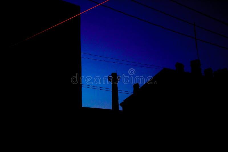 屋顶夜剪影有管子和电线的 库存图片