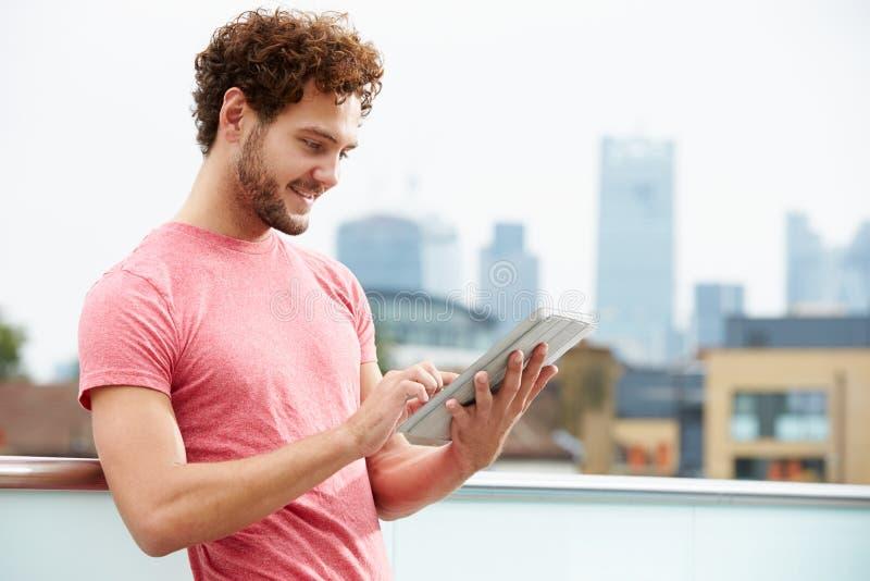 屋顶大阳台的人使用数字式片剂 免版税库存照片