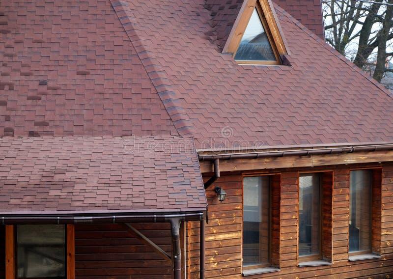 屋顶沥青木瓦和顶楼有双重斜坡屋顶的房屋窗口 屋顶建筑 屋顶修理 雨天沟 免版税库存图片
