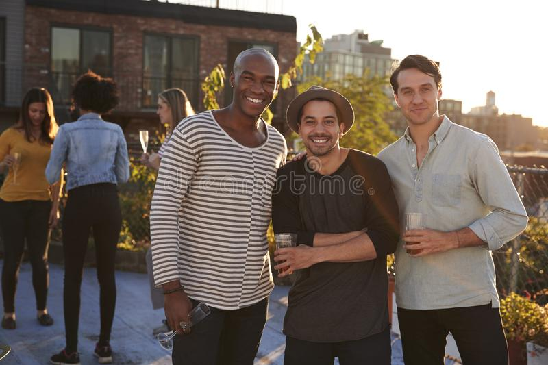 屋顶的三个男性朋友集会微笑对照相机 图库摄影