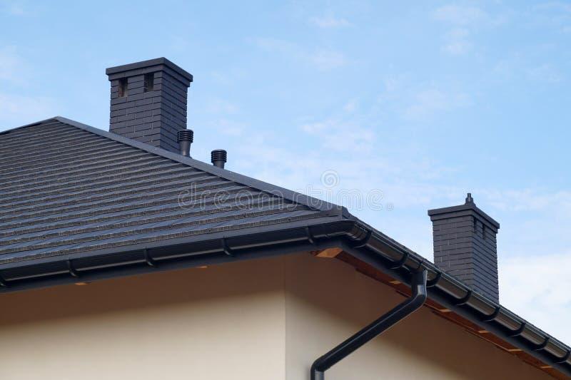 屋顶的片段由金属瓦,新的烟囱制成 一个最近建造的住宅房子 库存图片