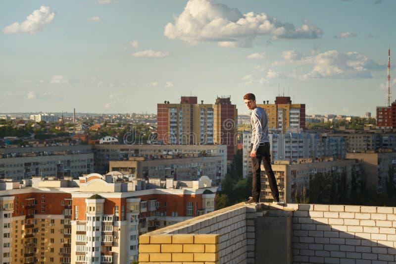 屋顶边缘的盖屋顶的人  免版税库存照片