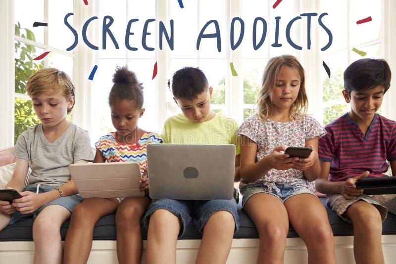 屏幕使用技术的上瘾者孩子 免版税库存照片