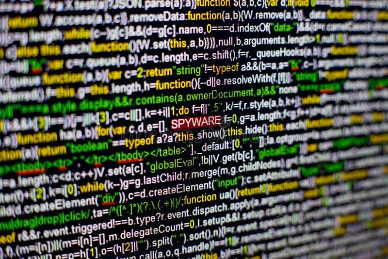 屏幕和被突出的间谍软件题字宏观照片有节目原始代码的在中部 在的剧本 免版税库存图片