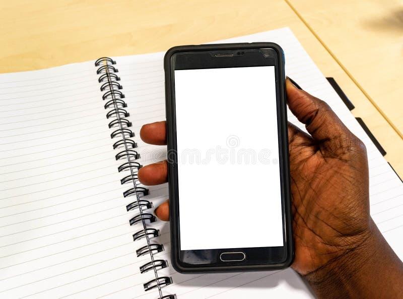 屏幕手机,在非洲妇女的手上 办公室藏品智能手机的黑人女性使用电子小配件笔记本 免版税库存图片