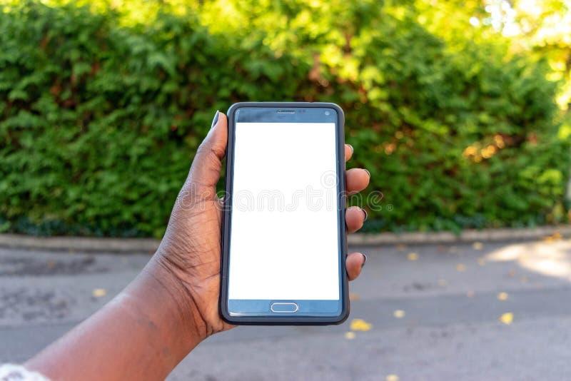 屏幕手机,在非洲妇女的手上 在绿色室外背景的黑女性举行的智能手机与空白的拷贝s 免版税图库摄影