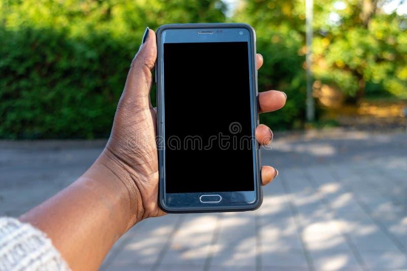 屏幕手机,在非洲妇女的手上 在绿色室外背景的黑女性举行的智能手机与空白的拷贝s 免版税库存照片