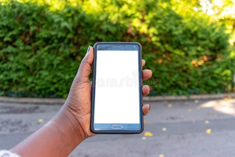 屏幕手机,在非洲妇女的手上 在绿色室外背景的黑女性举行的智能手机与空白的拷贝s 免版税库存图片
