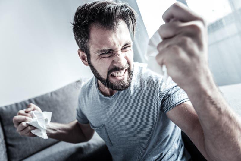 展示他的情感的恼怒的有胡子的人 库存照片