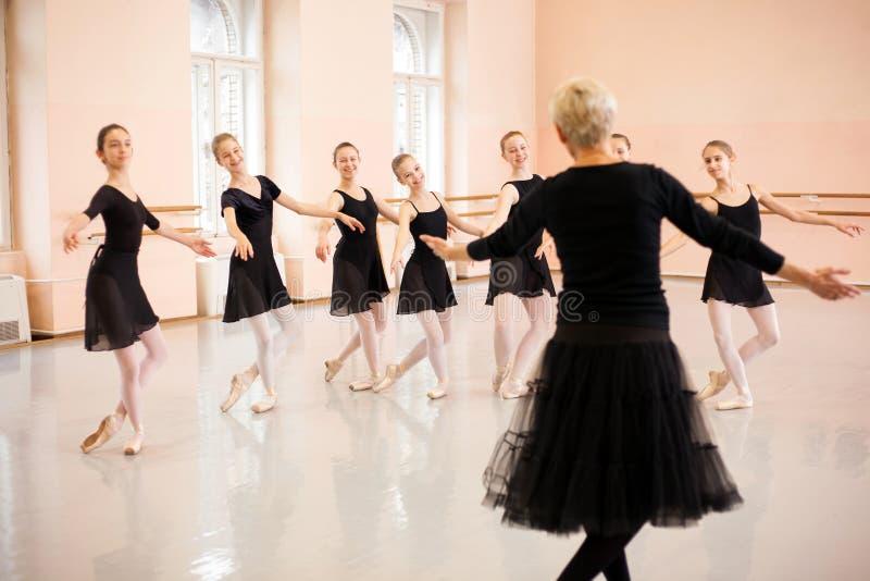 展示在一个小组的资深芭蕾辅导员移动十几岁的女孩前面 免版税库存图片