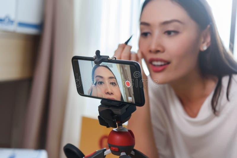 展示如何的秀丽博客作者应用眼线膏和由智能手机回顾在直播的产品社会媒介的,生活  免版税库存图片
