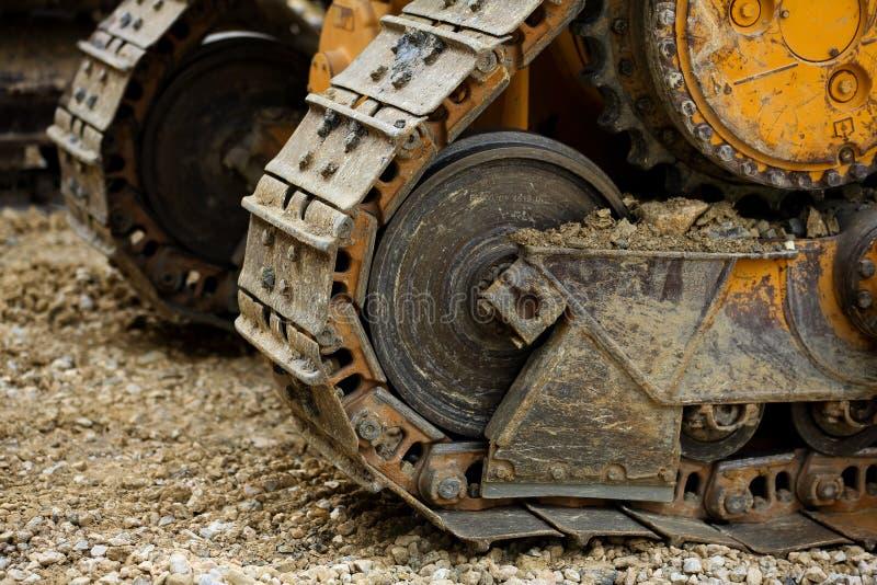 履带牵引装置关闭,在土质ambi的泥泞的履带牵引装置链子细节 免版税库存照片