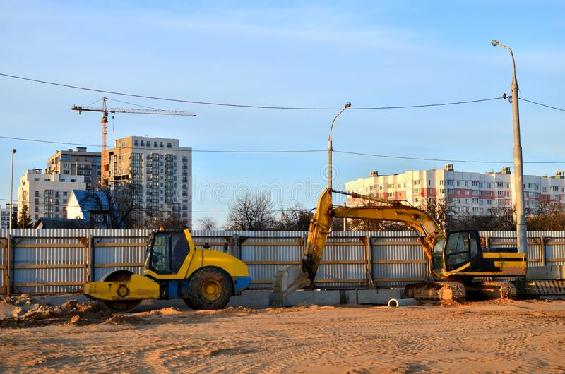 履带牵引装置挖掘机和摊铺机在工地工作 免版税库存照片