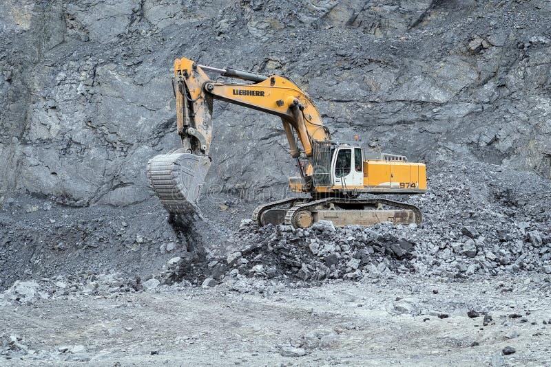 履带牵引装置挖掘机Liebherr,当解决在猎物,反对一个岩石倾斜的背景时 库存图片