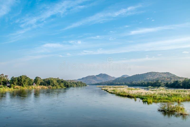 山、树、草、河的景观 免版税库存图片