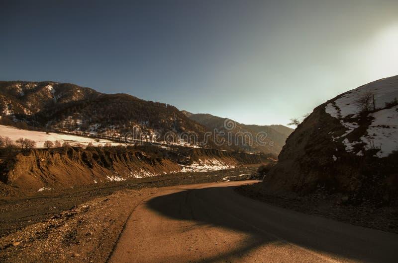 山、秋天或者冬天风景风景看法与五颜六色的小山的在日落 黄色草甸和Azerbaij多雪的山  库存照片
