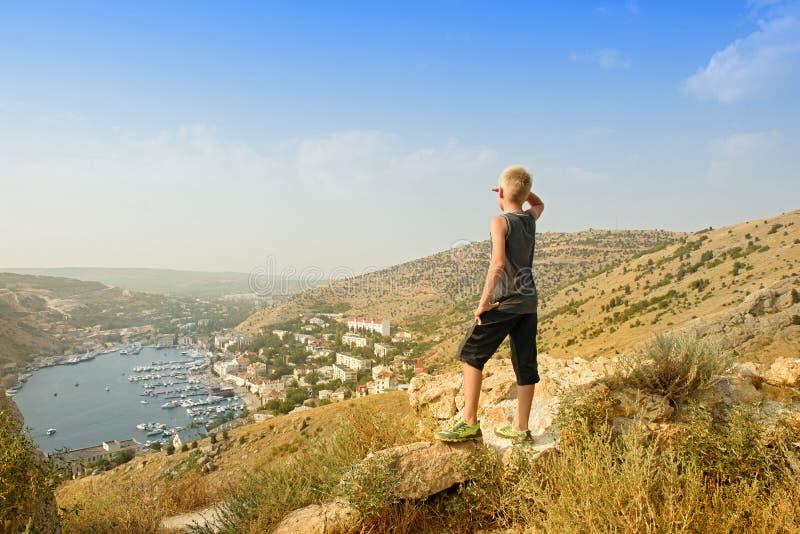 山上面的少年 与游艇和小船的海湾 旅行 库存图片