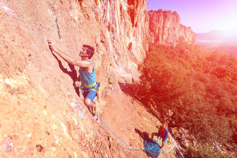 登山人人和有绳索和齿轮的妇女上升的橙色明亮的岩石墙壁队  库存照片