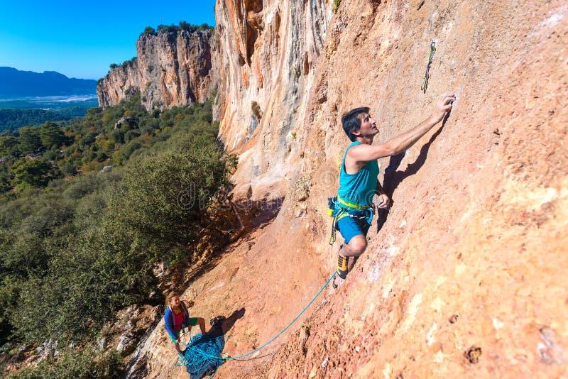 登山人人和有绳索和齿轮的妇女上升的橙色明亮的岩石墙壁队  免版税库存照片