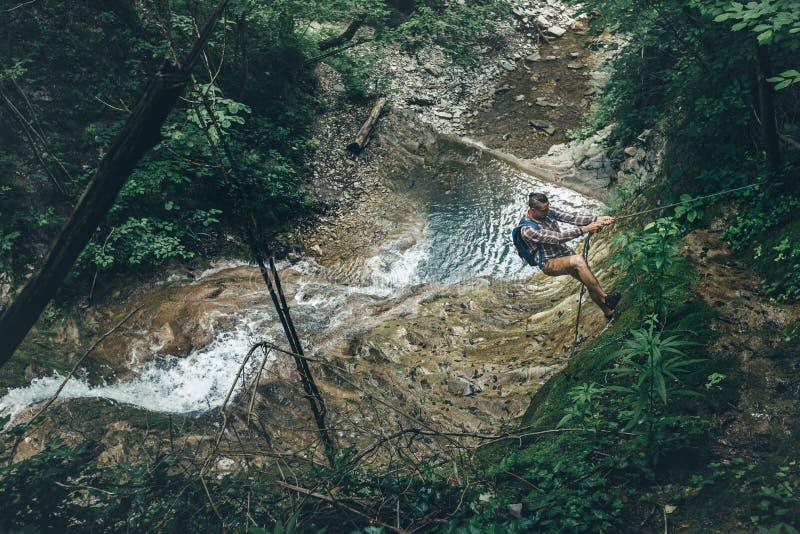 登山人人攀登在远足山冒险概念的瀑布背景的小山 免版税库存照片