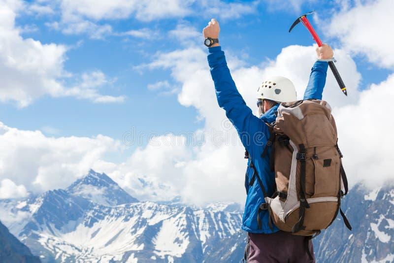登山人在一个岩石顶部用他的被举的手 免版税库存图片