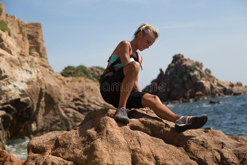 登山人女孩坐与海洋的峭壁在背景中 免版税库存图片