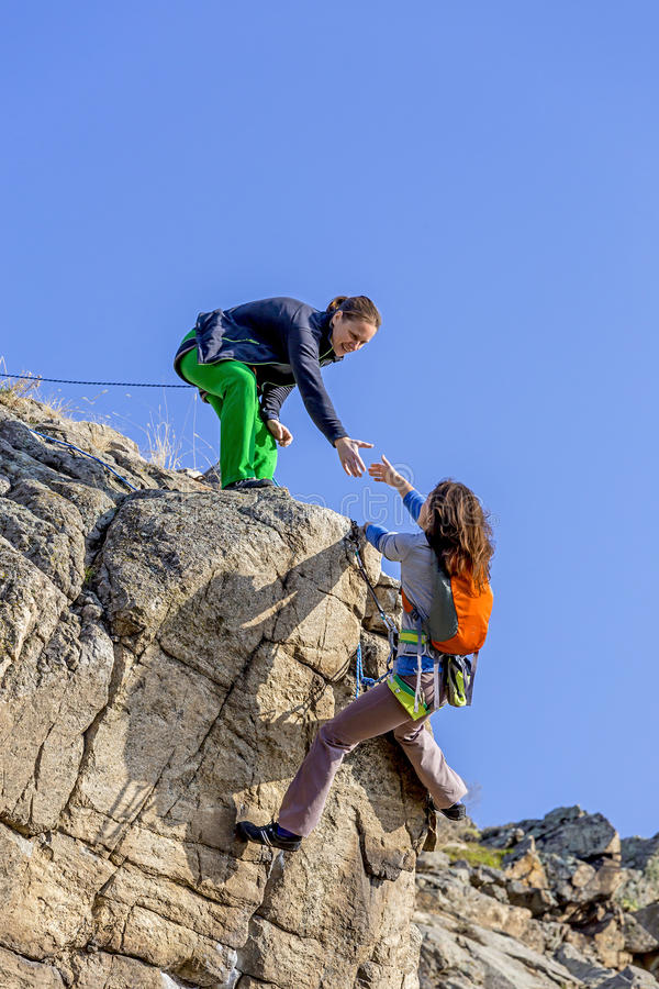 登山人帮助她的伙伴给富有山顶 库存照片