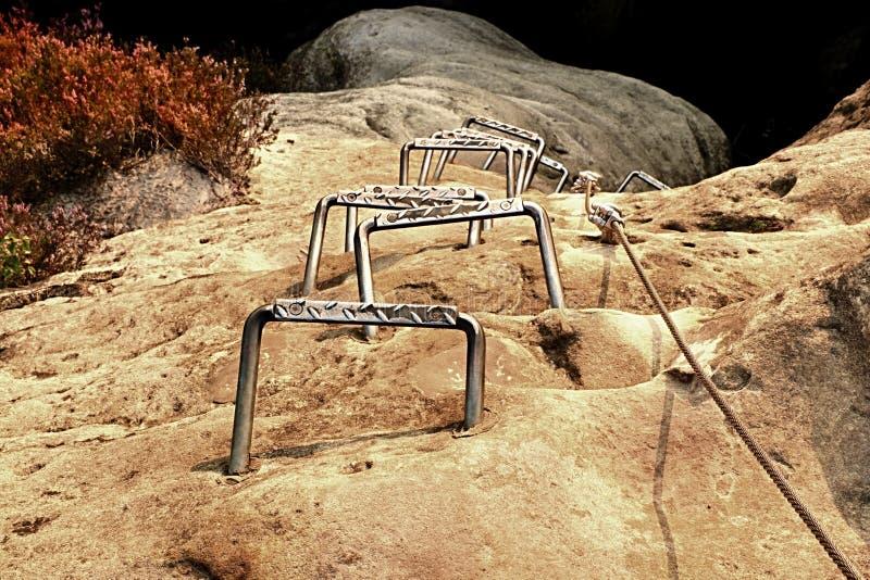 登山人金属梯子通过ferrata 电烙在块固定的扭转的绳索由螺丝短冷期勾子 绳索末端停住入砂岩大鹏 库存照片