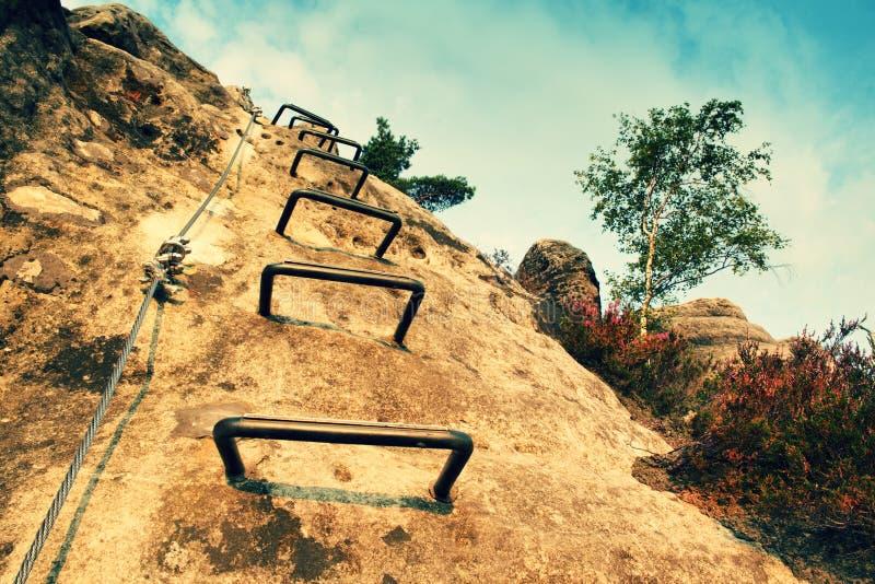登山人金属梯子通过ferrata 电烙在块固定的扭转的绳索由螺丝短冷期勾子 绳索末端停住入砂岩大鹏 库存图片