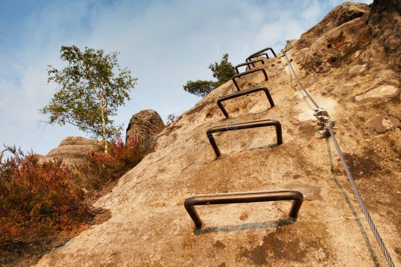 登山人金属梯子通过ferrata 电烙在块固定的扭转的绳索由螺丝短冷期勾子 绳索末端停住入砂岩大鹏 免版税库存照片
